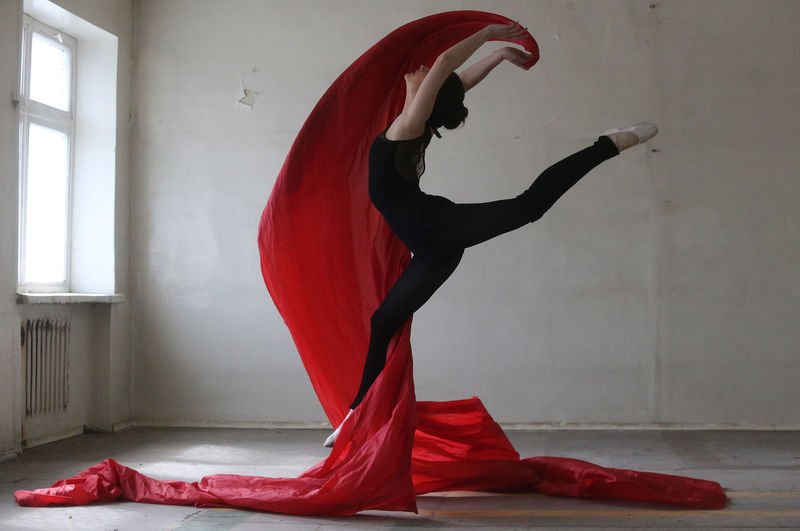 Young woman doing ballet dance with red fabric
