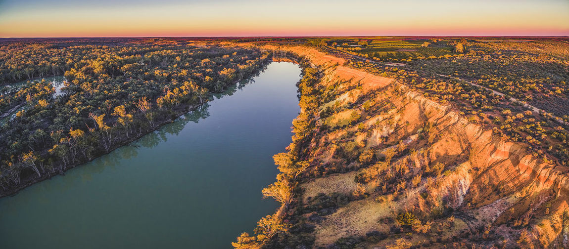 High angle view of river and landscape against sky during sunset