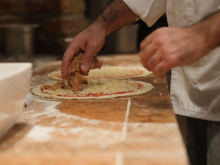 Midsection of chef preparing pizza at table in kitchen