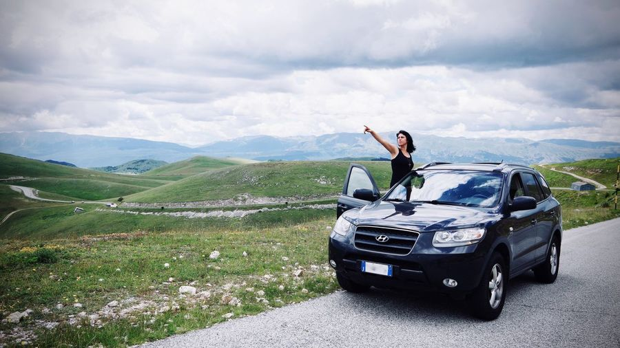 Woman standing by car on landscape against sky