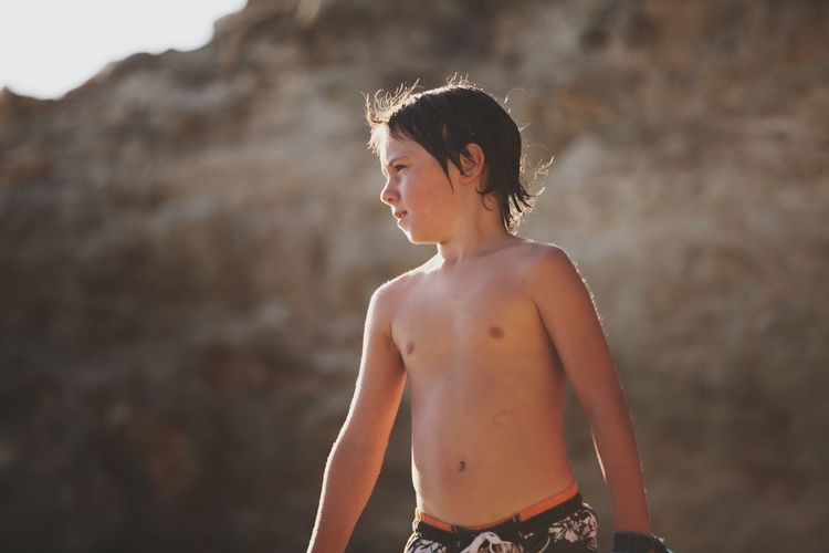 Portrait Of Shirtless Boy By Water