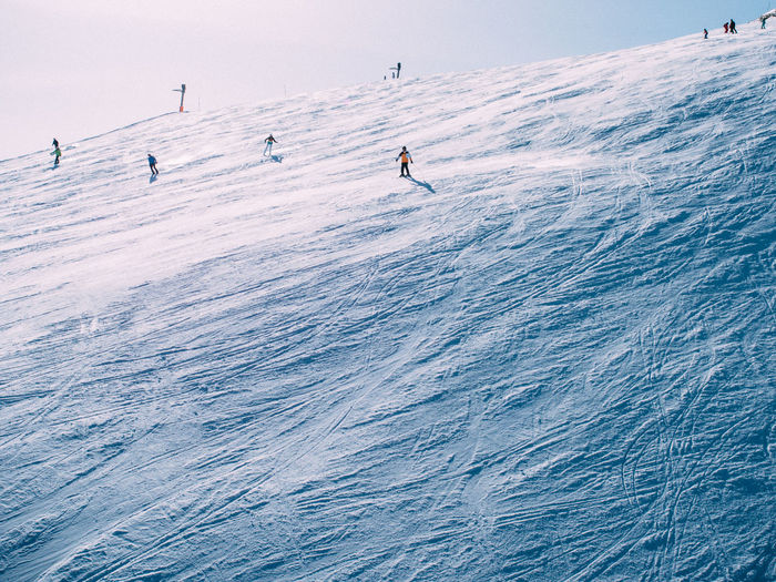 People skiing  on snow covered landscape against sky