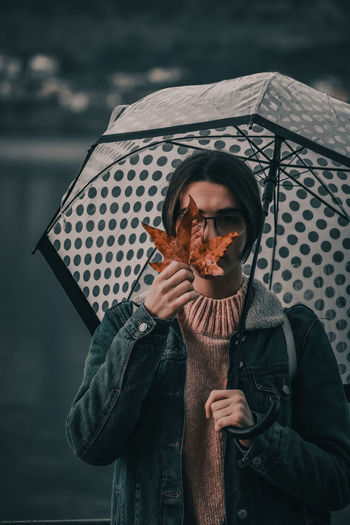Portrait of teenage girl holding umbrella and maple leaf while standing outdoors