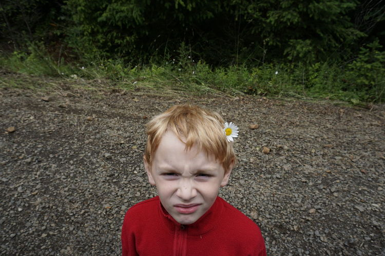 Portrait of boy wearing flower while standing on field