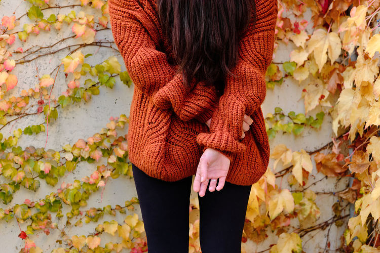 Low section of woman standing on leaves during autumn