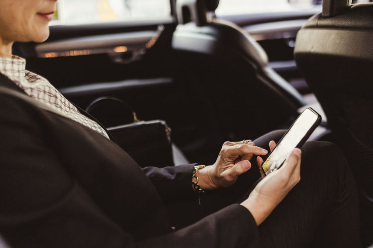 Midsection of woman using mobile phone while sitting in car