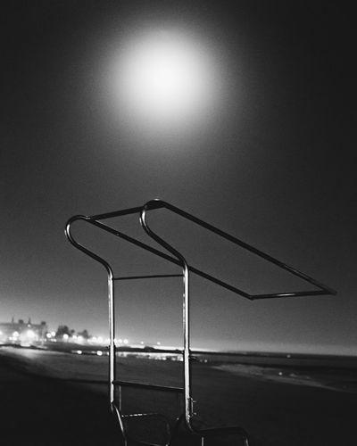 Illuminated street light on beach against sky