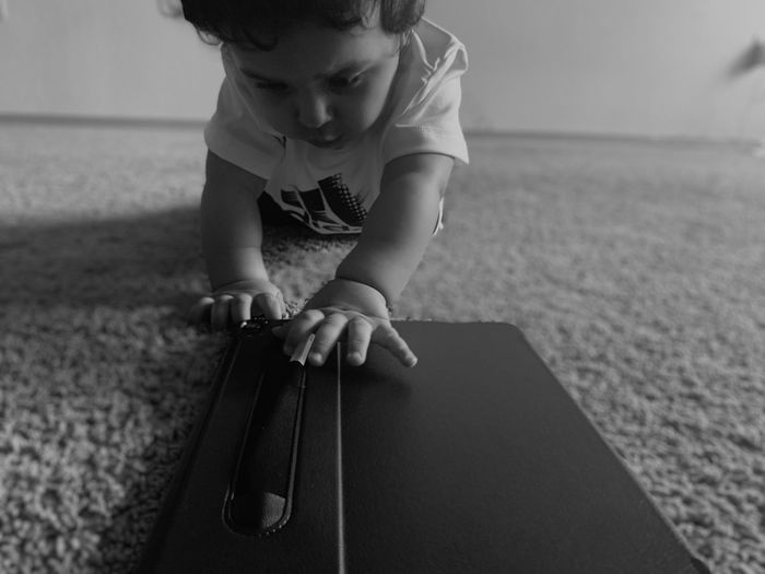 Cute baby girl touching digital tablet on floor at home