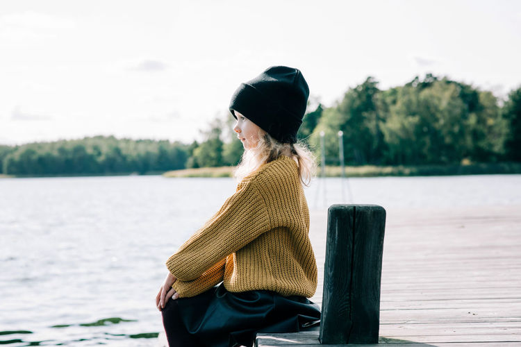 Side view of woman standing by lake against sky
