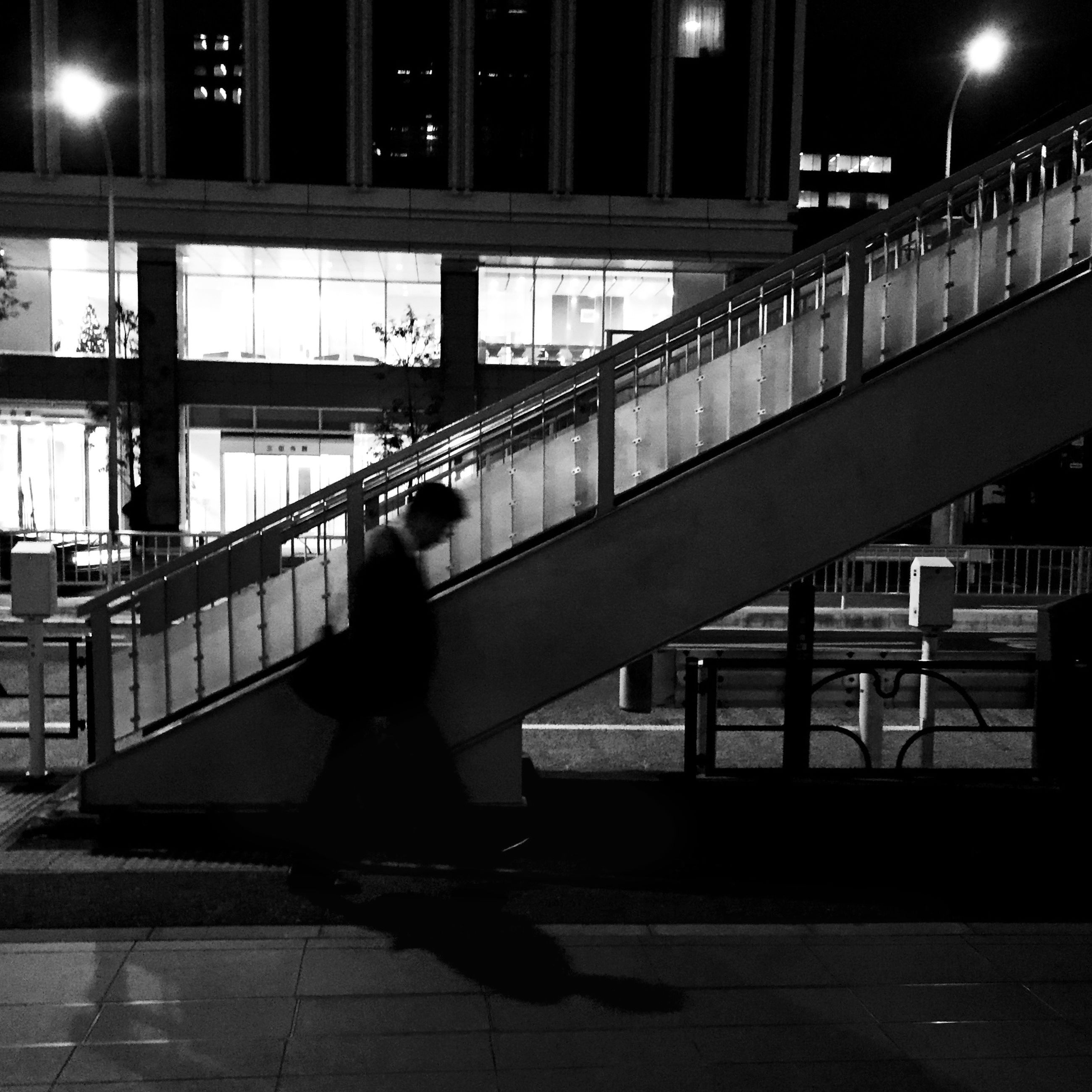 lifestyles, full length, illuminated, built structure, architecture, night, leisure activity, men, walking, building exterior, city life, city, standing, railroad station platform, person, casual clothing, rear view, railroad station