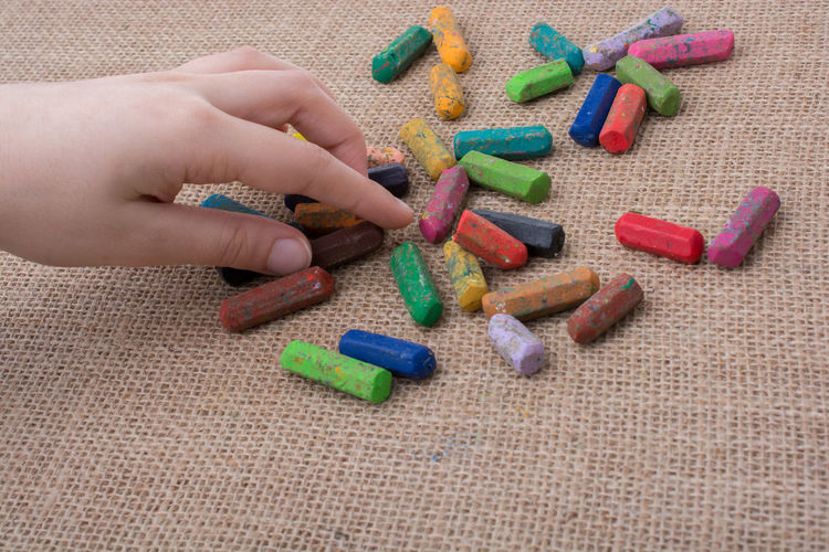 Used color crayons and a hand holding one Color Portrait Coloring Crayons Preschool Art Close-up Day Education Hand Holding Flower Human Body Part Human Finger Human Hand Indoors  Large Group Of Objects Multi Colored One Person People Real People