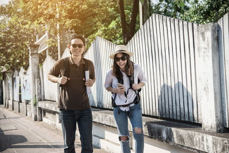 Happy man and woman walking with backpack on footpath