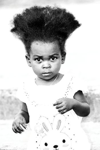 Portrait Of Cute Girl With Afro Hair Standing Outdoors