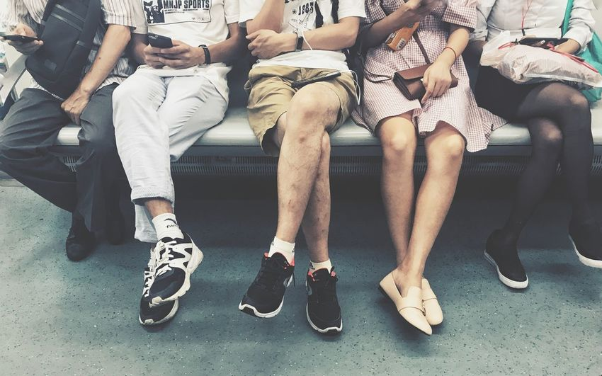 Low section of people sitting on bench in waiting room
