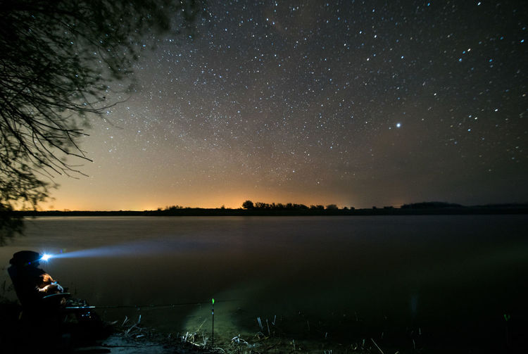 Man flashing light on lake against sky at night