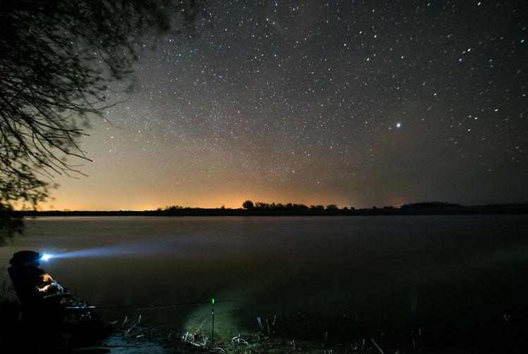 Man Flashing Light On Lake Against Sky At Night