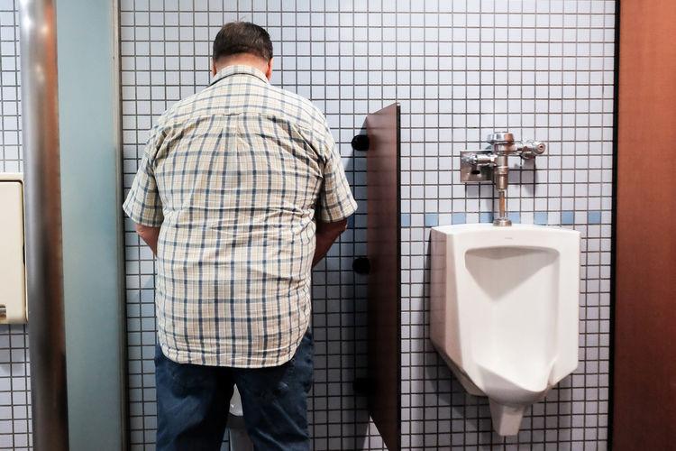 Rear view of man standing in bathroom