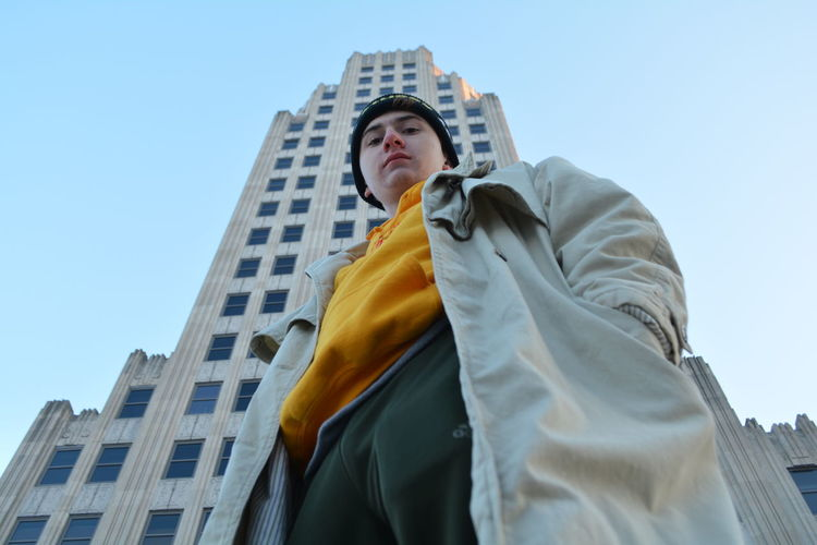 Low Angle Portrait Of Man Standing Against Building In City