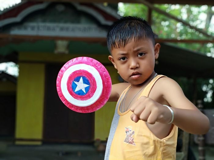 Portrait of cute boy with small shield standing at yard