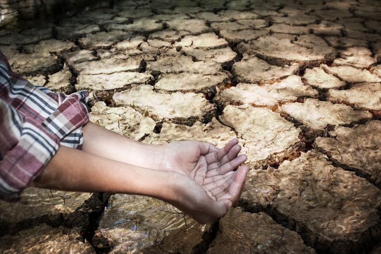 Cropped Hands Watering Wet Barren Land