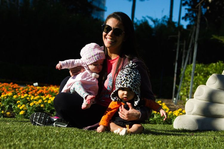 Happy mother with daughters sitting on grassy field at park