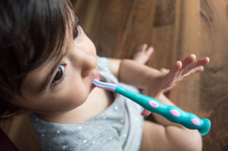 High angle view of cute girl with toothbrush in mouth sitting on floor