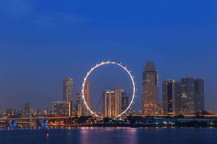 Illuminated ferris wheel by river and buildings against clear blue sky