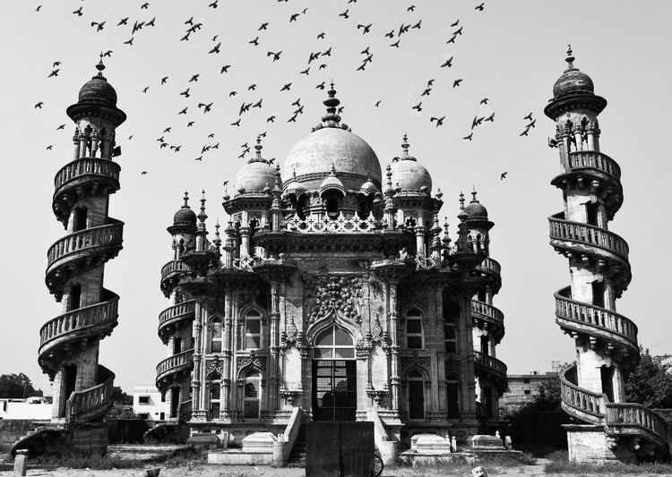 Flock Of Birds Flying Over Mahabat Maqbara Against Sky