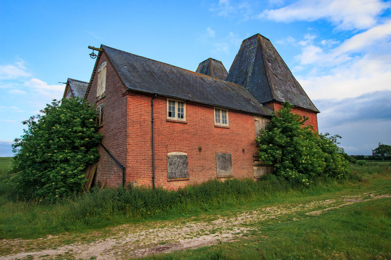 Oast House, Garden Of England, Kent, England. Architecture Sky Built Structure Nature No People Plant Hops Beer Brewing Iconic Buildings Vivid International Getty Images EyeEm Gallery Travel Destinations Tourism Sunrise Countryside Rural Scene History Building Exterior Building Tree Cloud - Sky House Day Land Field Growth Landscape Residential District Grass Outdoors Cottage