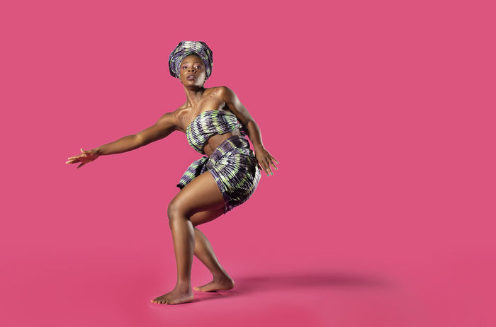 Beautiful African Black girl wearing traditional colorful African outfit does a dramatic dance move against a colorful pink background African African Traditions Adult African Dancer African Woman  Beautiful Woman Beauty Clothing Colored Background Dandelion Fashion Full Length Hairstyle Human Body Part Indoors  Looking At Camera One Person Pink Background Pink Color Portrait Studio Shot Tradition Dress Women Young Adult