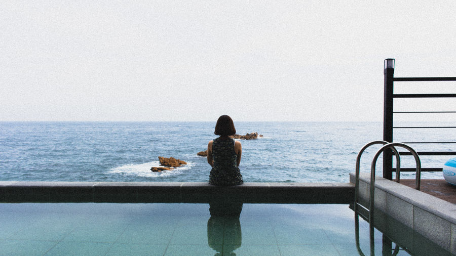 Woman sitting by infinity pool against sea against clear sky