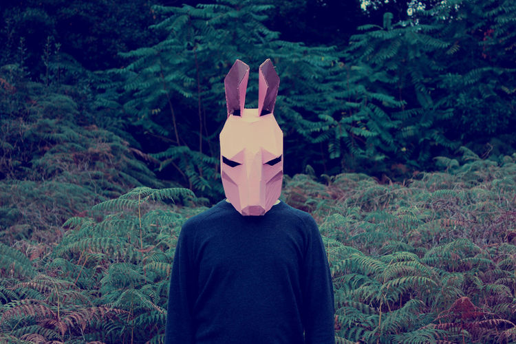 Man wearing mask standing against plants