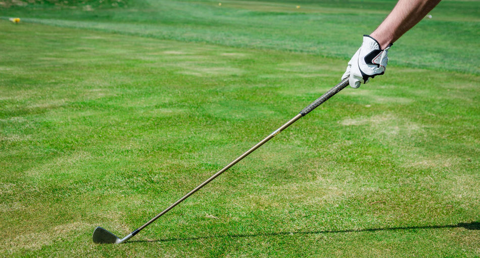 Cropped hand of man holding golf club