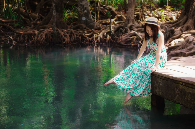Hipster woman sitting on Wooden bridge to the jungle, Tha pom mangrove forest, Beautiful Emerald Pool in mangrove forest at Krabi in Thailand. Song ñam Pom Tha Khlong Mangrove Beautiful Nature Forest Thailand Green Krabi Water Plant Landscape Tree På Phru Park Stream Thapom Background Outdoor Environment Blue Summer ASIA White Swamp Area Peat Canal View Country Pond Travel Color Pavilion Wooden Pool Emerald Jungle Healthy Natural Reflection Tropical Clear Root Leaf Wood