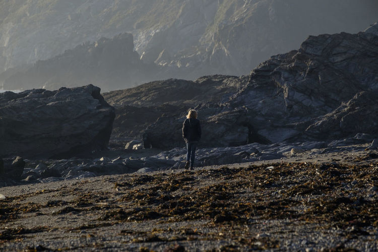 Rear view of woman walking at beach against rocky mountains