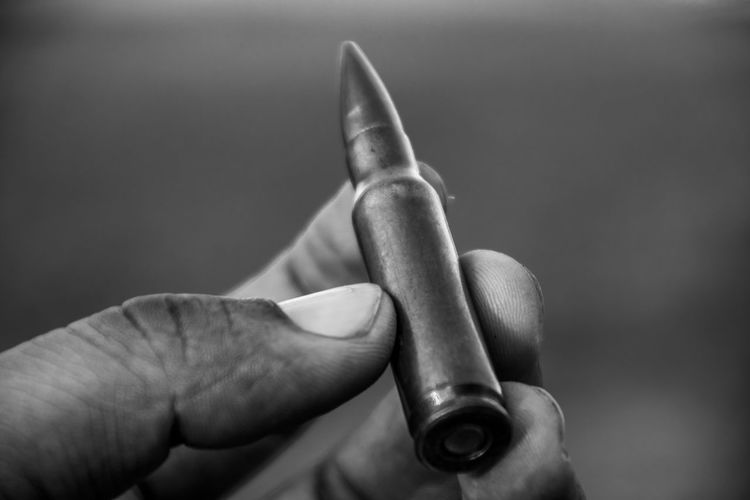 Close-up of hand holding bullet