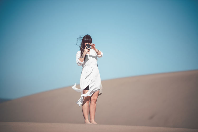 Full length of woman photographing mobile phone while standing at desert against clear sky during sunny day