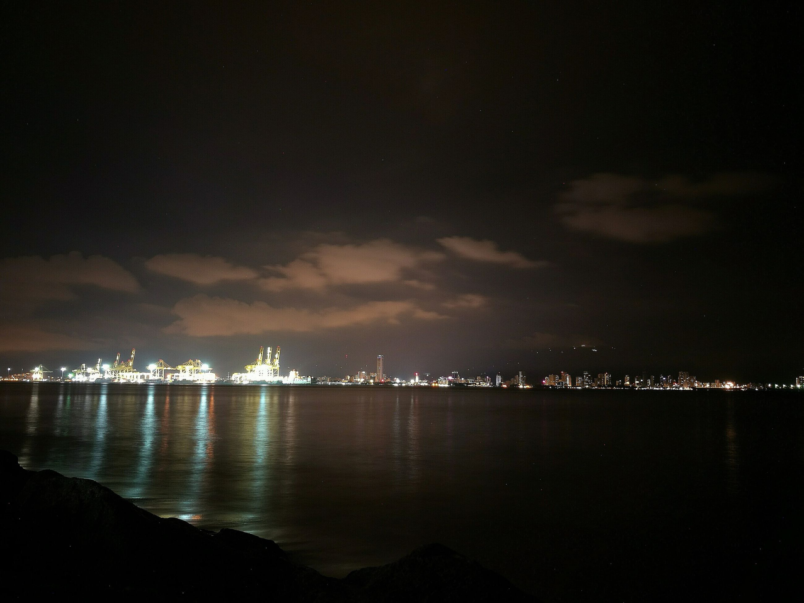 illuminated, city, water, architecture, night, building exterior, built structure, cityscape, sea, waterfront, sky, skyscraper, scenics, distant, reflection, cloud, tranquil scene, tranquility, skyline, outdoors, calm, city life, urban skyline, nature, cloud - sky, atmosphere, no people, development, ocean