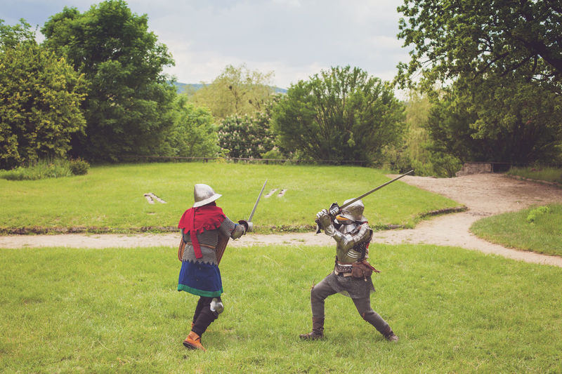 Two medieval knights in armor with swords and helmets are fighting on green grass Adult Battle Competition Day Fight Helmets Knights Lawn Meadow Medieval Outdoors Park Protection Summer Sword Tournament Tree