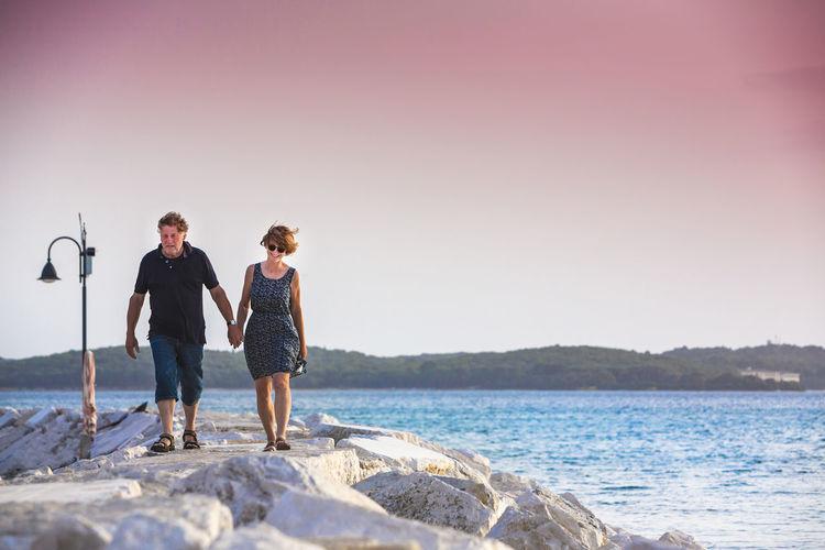 Full length of couple walking on pier by sea against clear sky