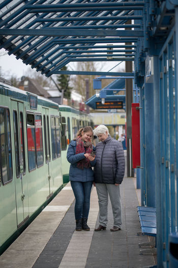 Adult Architecture Casual Clothing Couple - Relationship Full Length Lifestyles Men Mode Of Transportation People Public Transportation Rail Transportation Railroad Station Real People Senior Adult Senior Women Subway Train Train Train - Vehicle Transportation Travel Warm Clothing Women