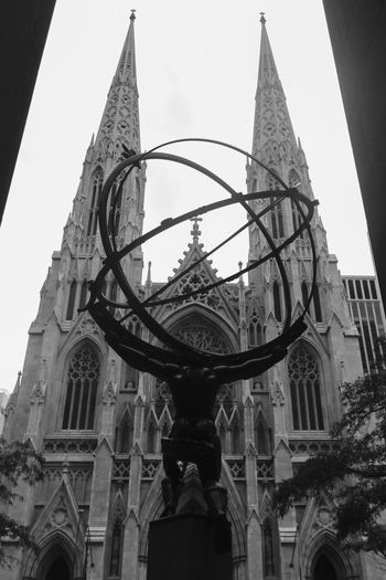Rockefeller Centre in New York. A Architecture Atlas Blackandwhite Blackandwhite Photography Building Exterior Built Structure City Day Dramatic History Low Angle View New York Outdoors Place Of Worship Real People Religion Sculpture Sky Spirituality St Patrick's Cathedral Statue Travel Destinations Urban Urban Geometry