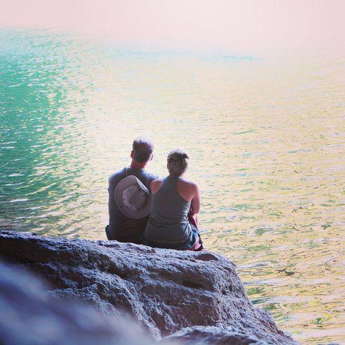 Rear view of people sitting on rocks
