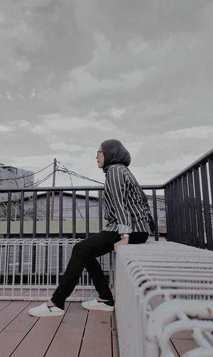 Side view of man standing on footbridge against sky