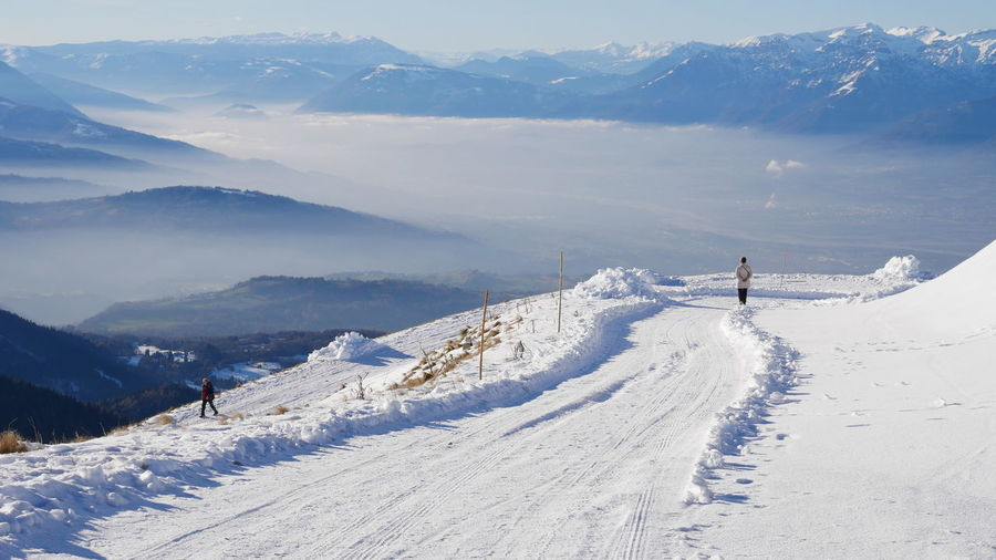 Panoramic view of people skiing on snowcapped mountains