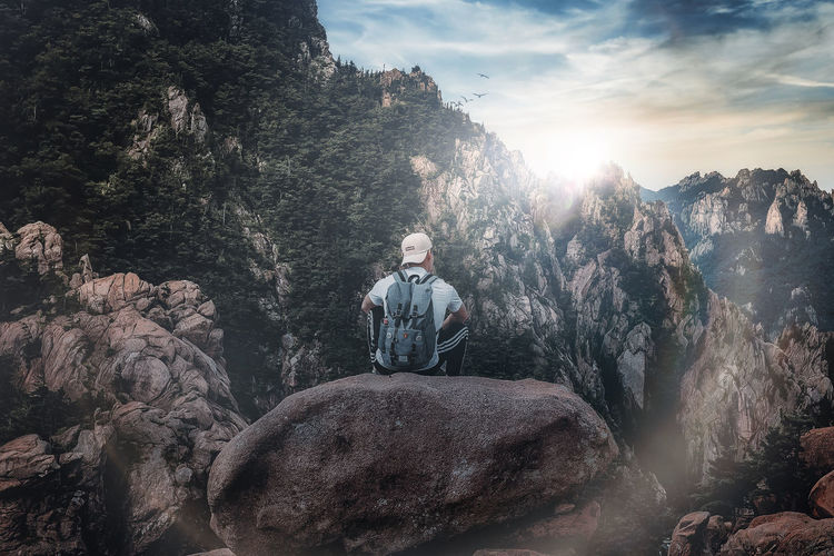 Man sitting on rock against mountain