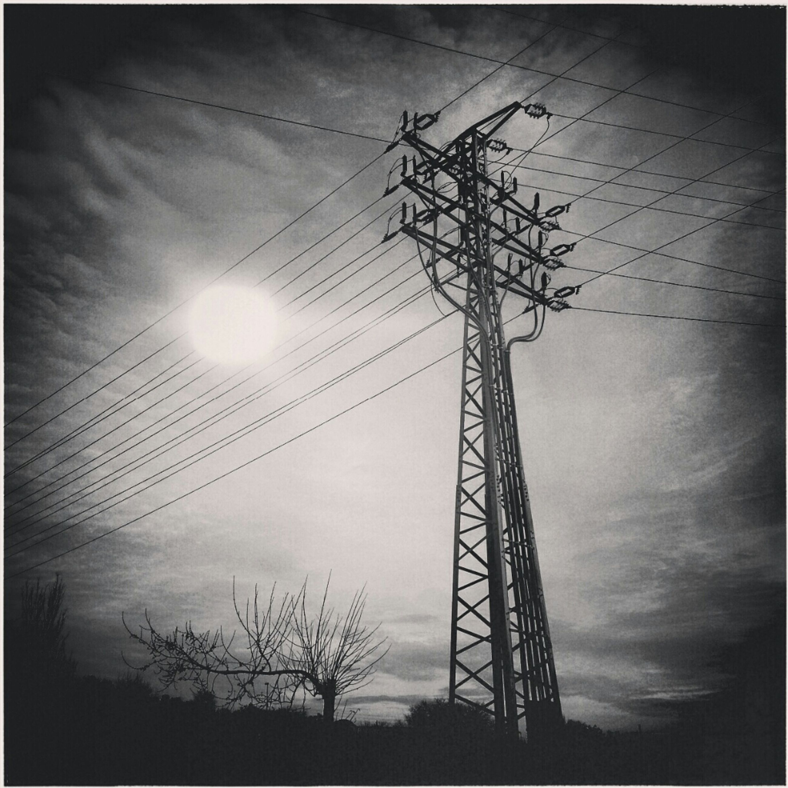 transfer print, silhouette, electricity pylon, low angle view, power line, power supply, electricity, fuel and power generation, sky, connection, sunset, auto post production filter, technology, sun, cable, cloud - sky, power cable, nature, outdoors, dusk