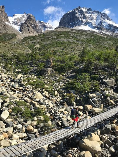 High angle view of woman walking on footbridge against mountain