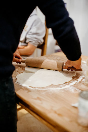 male hands rolling dough with a rolling pin in order to make a pizza Indoors  Food And Drink Food Nutrition Ingredient Ingredients Italia Italian Food Pizza Pizza Time Dough One Person Wood - Material Real People Preparation  Men Preparing Food Selective Focus Occupation Rolling Pin Table Making Working Standing Casual Clothing Kitchen Flour