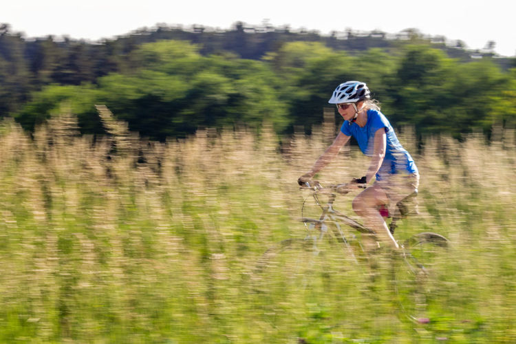 Woman bike ride Bike Ride Fahrrad Lady MTB Woman Activity Bewegungsunschärfe Bicycle Bike Field Grass Hopfen Leisure Activity Lifestyles Livestyle Nature One Person One Woman Only Outdoors Plant Real People Riding Sport Sports Velocity
